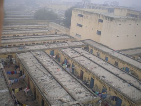 The Kapashera slum is divided into several compounds with rows of tiny ten-by-ten-foot one-room units. Each compound contains thirty to one hundred rooms. Photo: https://gurgaonworkersnews.files.wordpress.com/.