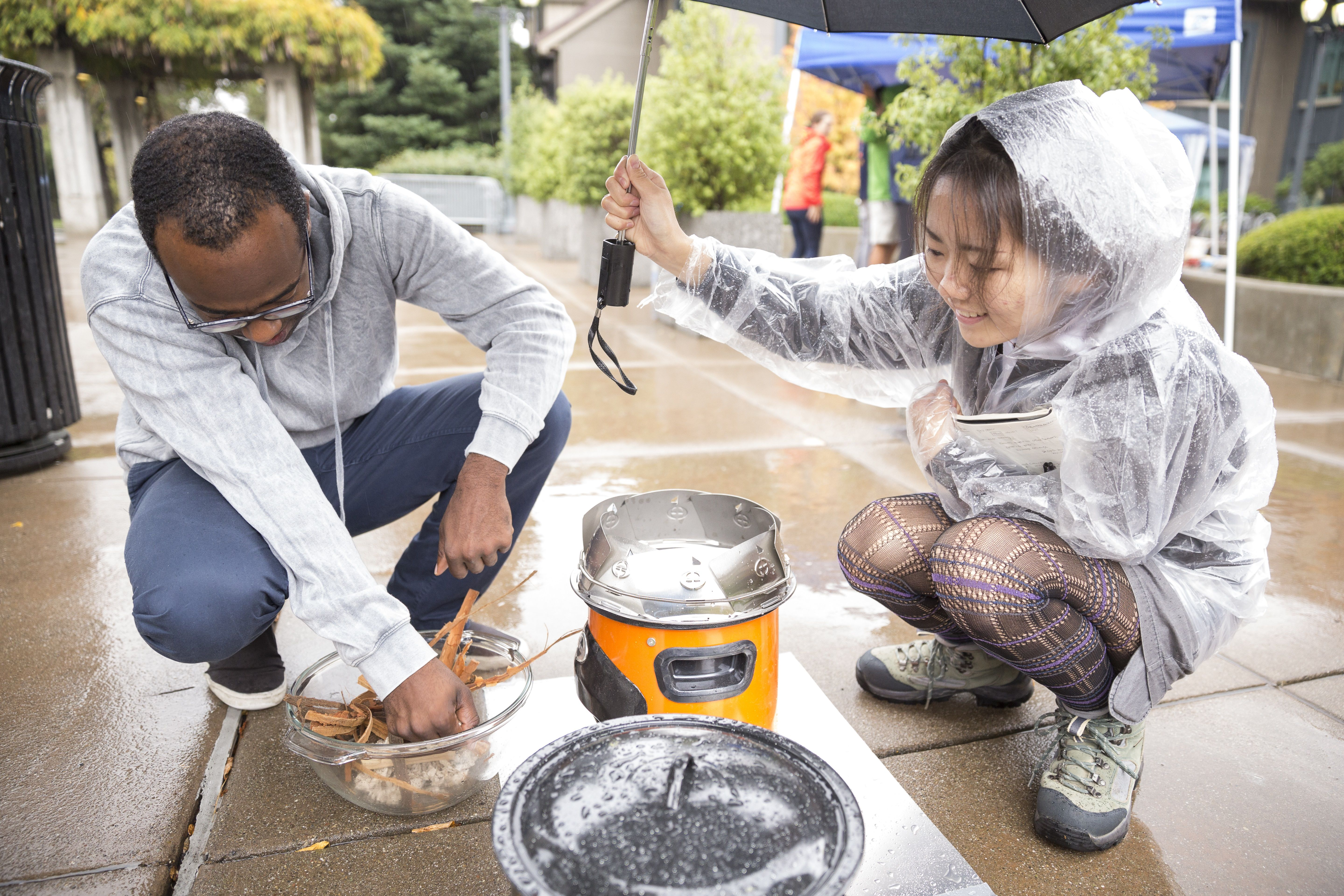 Two students work on a prototype of the Darfur stove in the rain