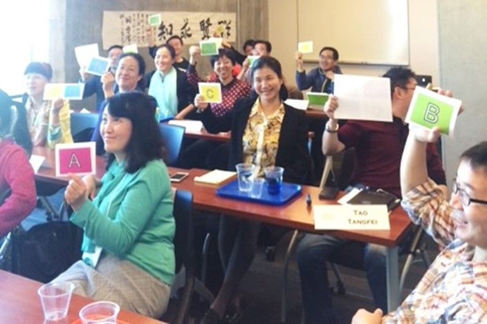 Participants from the China Program hold up cards they have made