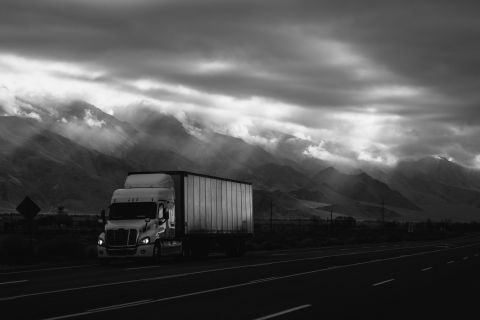 semi truck driving past mountains