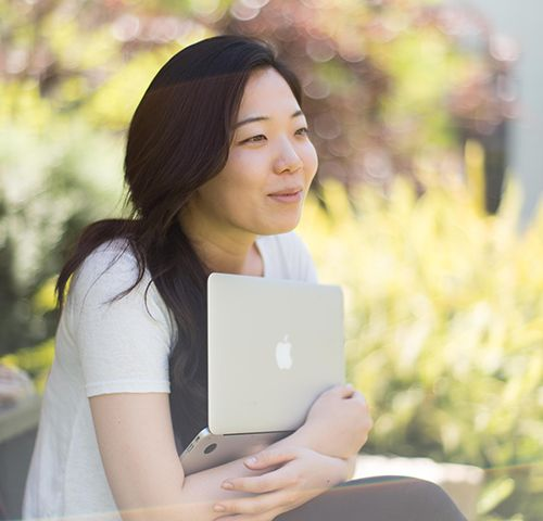 A student sits with her laptop in the courtyard